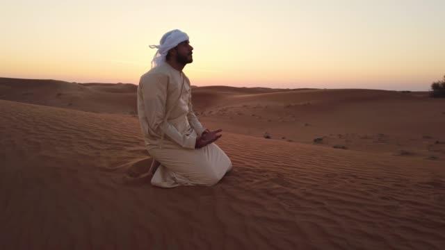 vídeos y material grabado en eventos de stock de oración árabe en una duna de arena - islam
