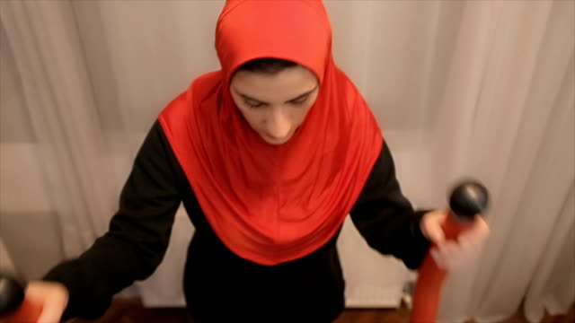 Arab woman is training at a sports exercise machine at home video