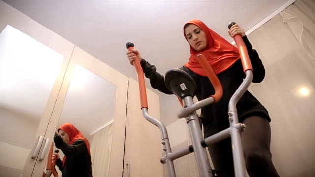 Arab woman is training at a sports exercise machine video