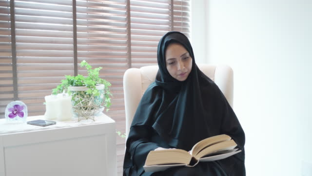 Arab woman reading a book in the home study