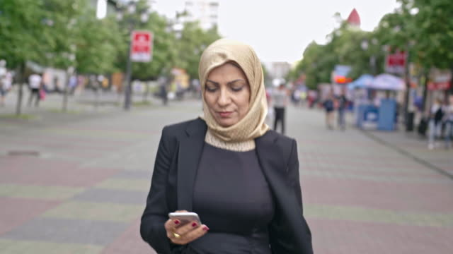 arab woman texting messaging on the move - abbigliamento modesto video stock e b–roll