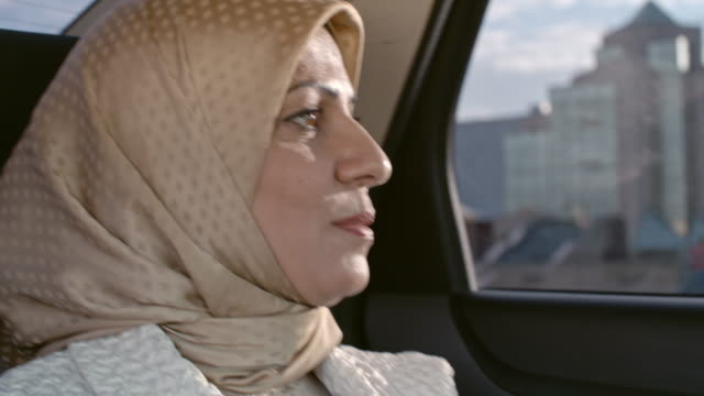 Arab woman thinking in back seat of car video
