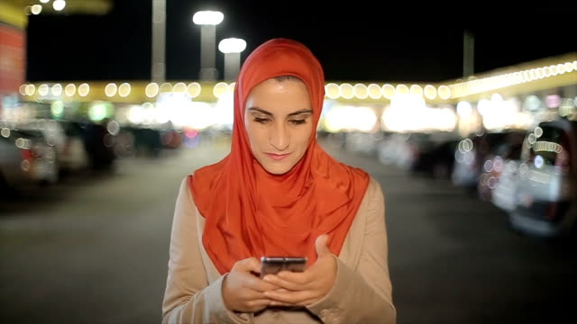 Arab woman using mobile phone on the street at night video