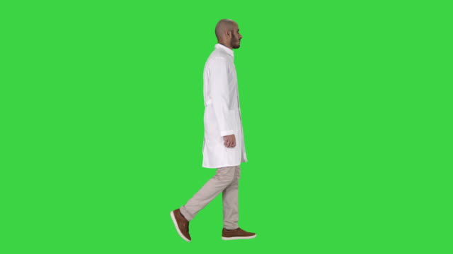Arabian doctor in white robe walking on a Green Screen, Chroma Key Full length shot. Side view. Arabian doctor in white robe walking on a Green Screen, Chroma Key. Professional shot in 4K resolution. 011. You can use it e.g. in your commercial video, business, presentation, broadcast full length stock videos & royalty-free footage