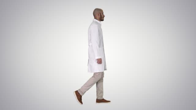 グラデーションの背景に歩いて白いローブでアラビアの医師 - 全身点の映像素材/bロール