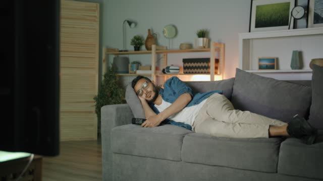 vídeos de stock, filmes e b-roll de homem árabe que dorme no sofá na frente da tevê que relaxa na noite no plano escuro - solteiros jovens