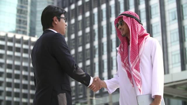 arabiska och kinesiska affärsmän handskakning. modern stad bakgrund. internationella affärer och utomeuropeiska samarbete. - kulturer bildbanksvideor och videomaterial från bakom kulisserna