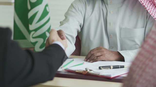 uomo d'affari arabo che stringe la mano al suo socio in affari - arabia saudita video stock e b–roll