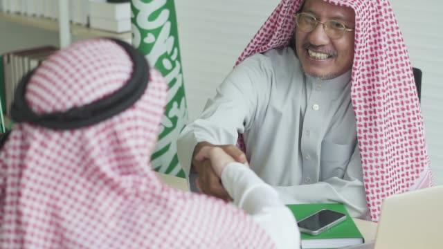 arabic businessman shaking hand with his business partner - arabia saudita video stock e b–roll
