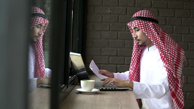 arabic businessman wearing islamic clothes working with notebook in the coffee shop. - arabia saudita video stock e b–roll