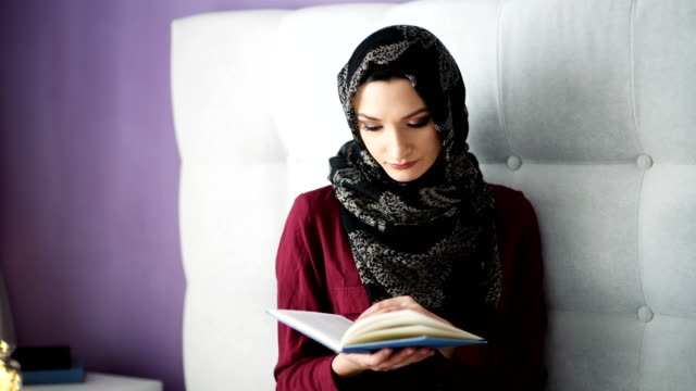 arabic woman in hijab reading a book - abbigliamento modesto video stock e b–roll