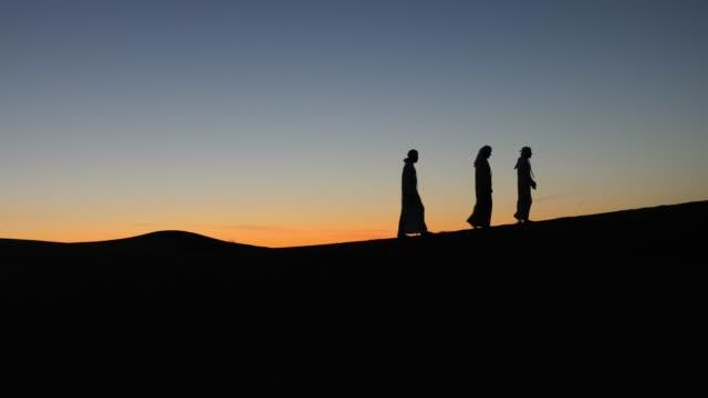 vídeos y material grabado en eventos de stock de árabes en el desierto en la cima de la duna de arena - islam