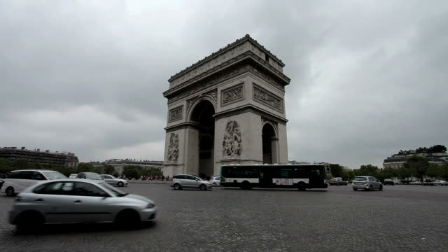 Arc De Triomphe on a cloudy day. Centered, still long shot. Cars and bus passing by. video