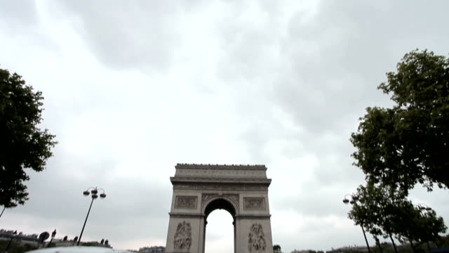 Arc De Triomphe on a cloudy day. Long shot, centered. Tilt from the sky to the Arc and back. Some traffic drives through. video