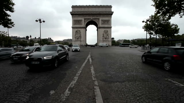 Arc De Triomphe on a cloudy day. Long shot, centered. Tilt from the ground to the Arc and to the sky. A lot of traffic drives through. video