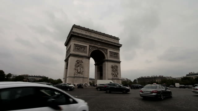 Arc De Triomphe on a cloudy day. Long shot, slight angle. Tilt from the ground to the Arc. A lot of traffic drives through. video