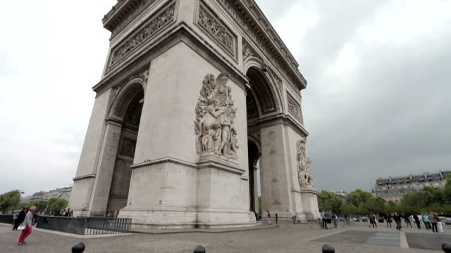 Arc De Triomphe on a cloudy day. Medium shot, corner. Tilt from the ground to the Arc. video