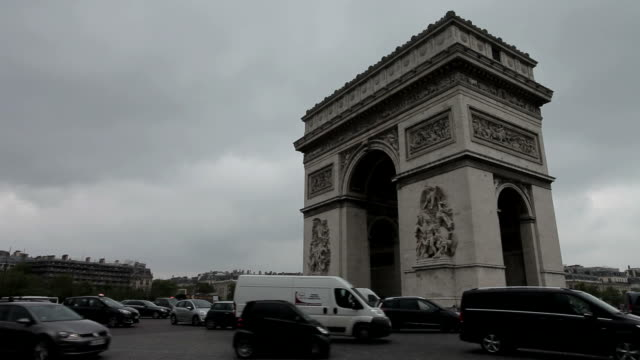 Arc De Triomphe on a cloudy day. Positioned right, still long shot. A lot of traffic drives through. video