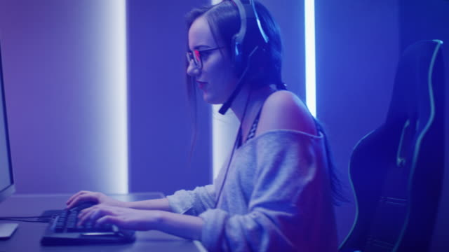 Arc Shot of the Beautiful Pro Gamer Girl Playing in First-Person Shooter Online Video Game on Her Personal Computer. Casual Cute Geek wearing Glasses and Headset. Neon Room. eSport Cyber Games Internet Championship Event.