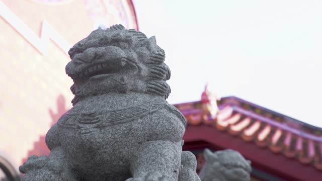 A arch camera move take of a gray stone carving lion set on a platform of a temple in Taiwan.