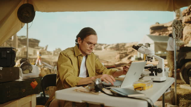 Archaeological Digging Site: Male Archaeologist Doing Indigenous Culture Research, Discovers Ancient Civilization Historical Artifacts, Fossil Remains at Excavation Site, Uses Laptop for Analysis.