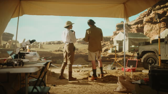 Archaeological Digging Site: Two Great Archeologists Work on Excavation Site, Inspect Newly Discovered Ancient Civilization Architectural Site, Looking into Binoculars, Planning Work and Strategy