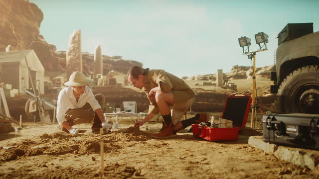 Archeological Digging Site: Two Great Archeologists Work on Excavation Site, Cleaning Cultural Artifacts with Brush and Tools. Discovery of Ancient Civilization Temple, Architecture, Fossil Remains