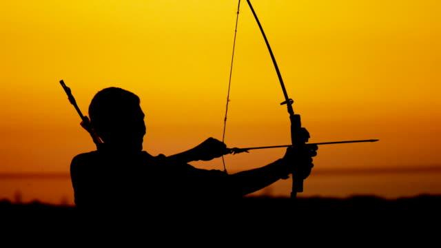 vidéos et rushes de archer au coucher du soleil. - tir à l'arc