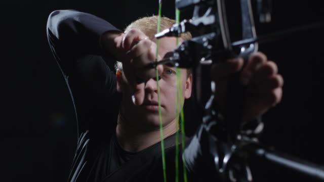 vidéos et rushes de archer tir flèche isolée sur fond noir - tir à l'arc