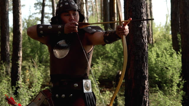 Archer with an eastern appearance aiming an arrow in forest video
