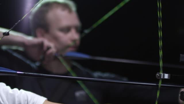 vidéos et rushes de archers qui vise et le tir des arcs sur fond noir - tir à l'arc