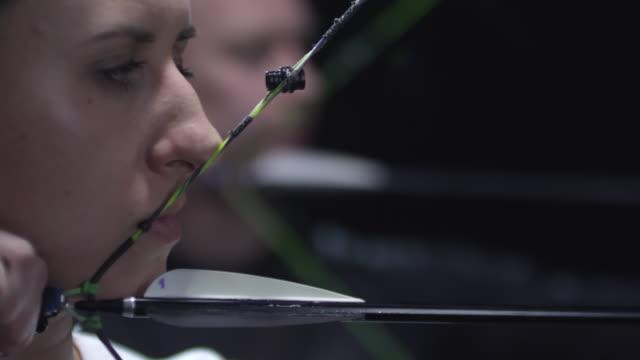 vidéos et rushes de archers tirant des flèches sur fond noir - tir à l'arc