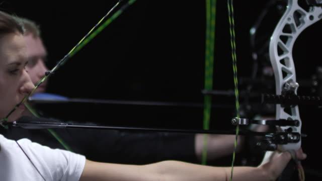 vidéos et rushes de archers tirant des arcs dans slowmo sur fond sombre - tir à l'arc