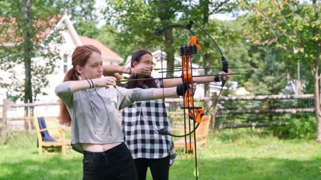 Archery at the backyard. Two teenager gilrs, sisters, shooting together. Pennsylvania, Poconos, USA video