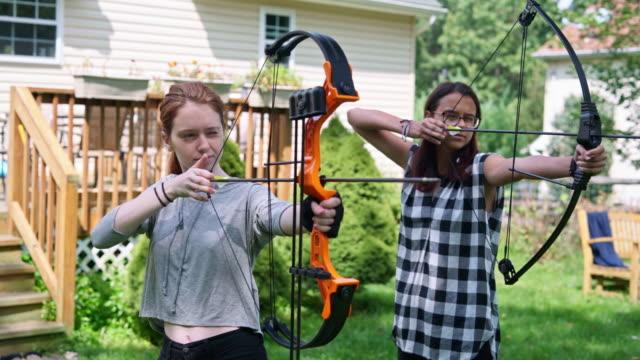 vidéos et rushes de tir à l'arc à l'arrière-cour. deux adolescent gilrs, soeurs, tournage ensemble. pennsylvanie, poconos, é.-u. - tir à l'arc