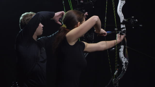 vidéos et rushes de tir à l'arc athlètes décochant des flèches sur fond noir - tir à l'arc