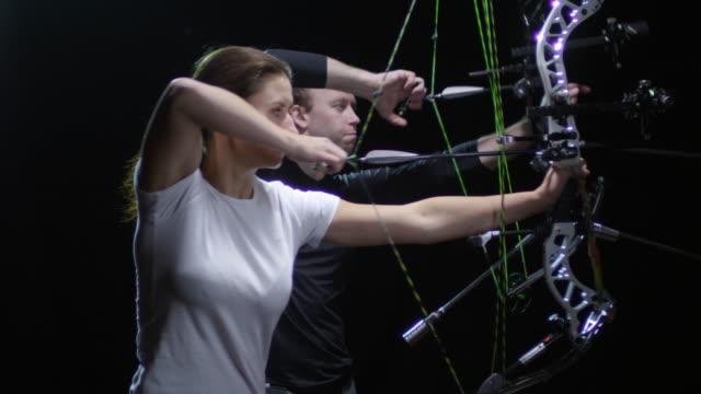 vidéos et rushes de athlètes de tir à l'arc tir arc sur fond noir - tir à l'arc