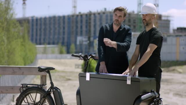建築家および建設労働者の貨物のバイクに建物の計画を議論します。 - プロジェクトマネージャー点の映像素材/bロール