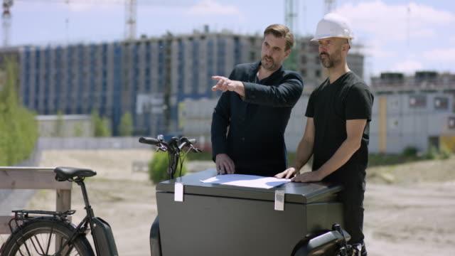 建築家および建設労働者の貨物のバイクに計画を議論 - プロジェクトマネージャー点の映像素材/bロール