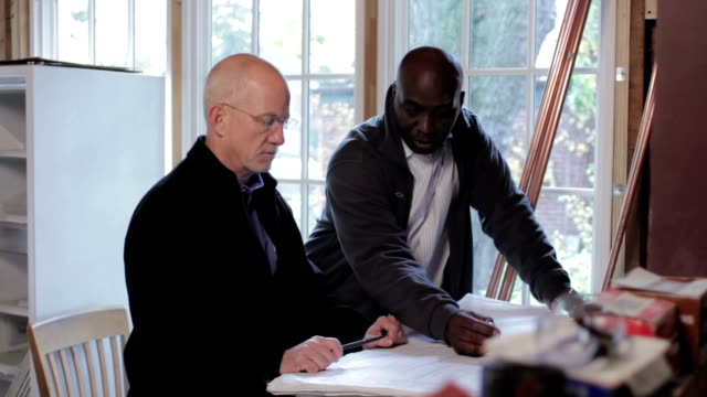 Architect and contractor looking at renovation plans video