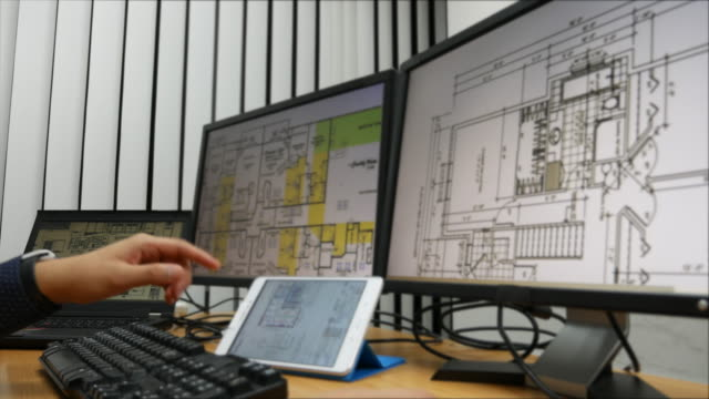 Architect at work with plan with computer video