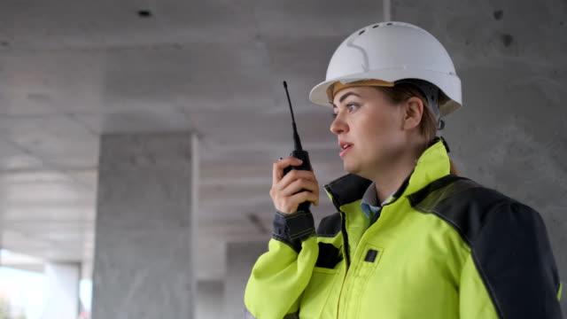 arkitekt byggare pratar i radio byggnaden under uppbyggnad. ingenjör i vit hård hatt - kvinna ventilationssystem bildbanksvideor och videomaterial från bakom kulisserna