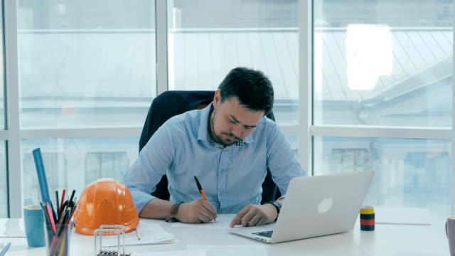 architekt, geschäftsmann in modernen hellen büro arbeiten am computer mit bauplan und pläne - kopfbedeckung stock-videos und b-roll-filmmaterial