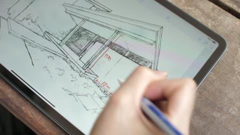 vidéos et rushes de architecte commenter les détails du plan de la chambre sur tablette numérique - architecte