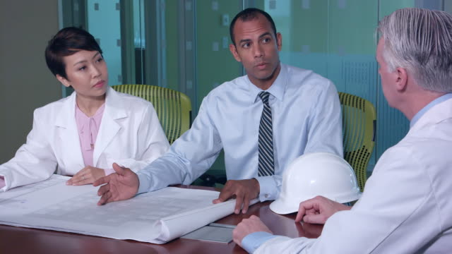 Architect Discusses Blueprints with Doctors and Managers video