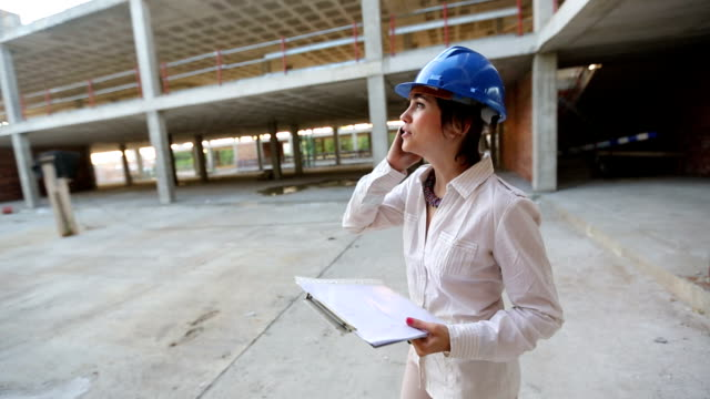 Architect having a mobile phone conversation at the construction site. video
