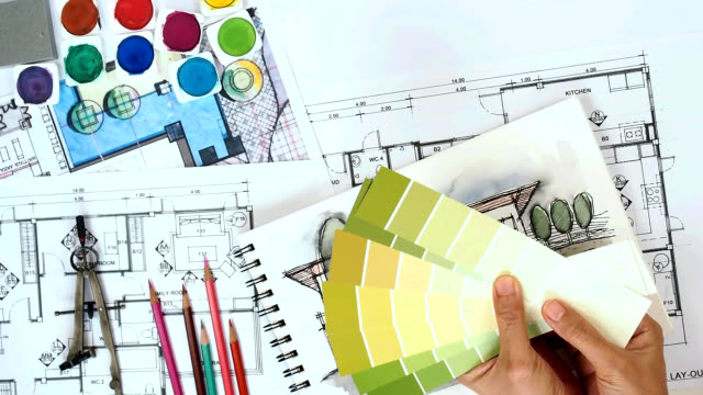 Architect & interior designer working at worktable with drawing, blue print, sample video