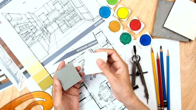 Architect & interior designer working at worktable with floor plan, blue print, sample video