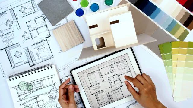 Diseñador arquitecto & interior trabajando en mesa de trabajo con casa modelo, tableta, impresión azul - vídeo