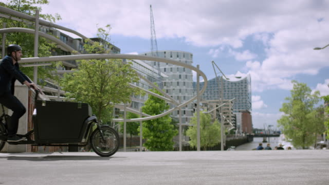 Architect is riding with his cargo bike through the city. Hamburg video